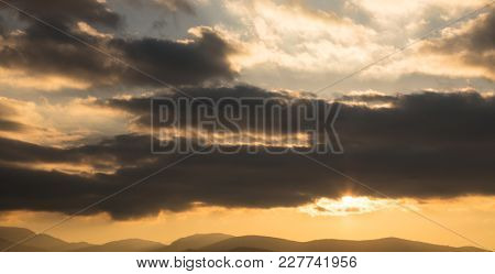 Sunrise or sunset over mountains silhouette. Sunbeams come through the colorful heavy clouds and lighten the sky and the hills. Space, banner.