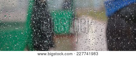 Rain drops are rolling on transparent window. Big drops reminds that autumn has arrived. Abstract, blurred background, close up view, banner, space for text.