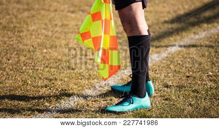 Football soccer arbiter assistant stands at sideline observing the match with flag at hands. Blurred green field background, close up.