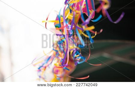Carnival party with colorful hanging streamers on blurred background. Close up view with details, space for text, banner