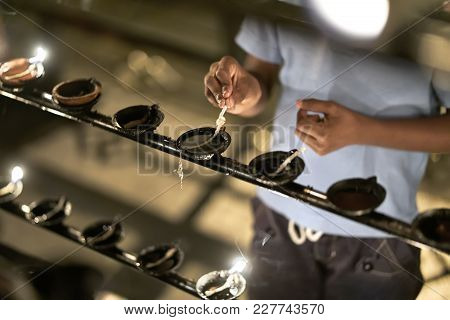 Man Is Holding A Wick Of An Oil Candle Which Is Standing On The Black Rack In The Buddhist Temple In