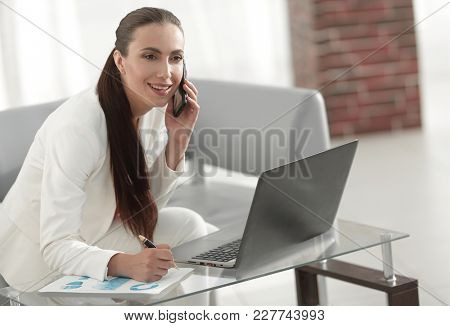businesswoman discussing financial charts on the phone