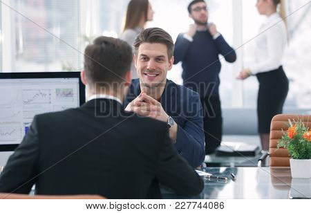 Two men discuss the growth of the company, looking at the rising graph on a computer screen