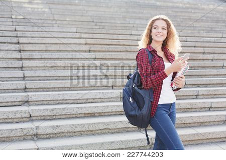 Beautiful Smiling Student Girl Standing With Notebook And Using Smarphone, Preparing For Exams Durin