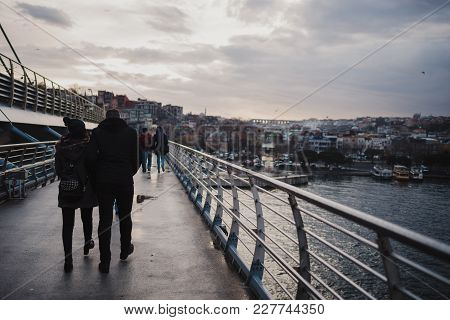 Istanbul, Turkey - February 14, 2018: People Of Istanbul Are Walking On The Bridge In A Cloudy Rainy