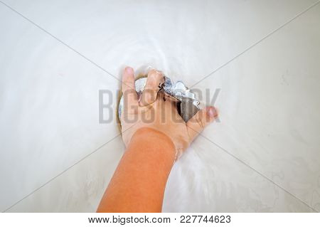 Hand Of A Young Child Tries To Stop The Water From Draining From The Bathtub.  Wants To Keep Bathing