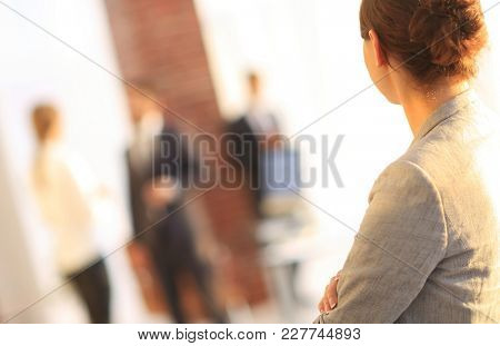 rear view of business woman on blurred background office.