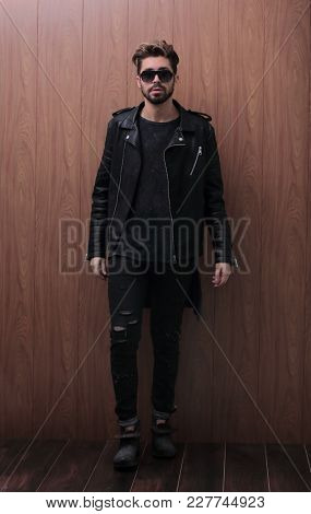 a man is standing in a black leather jacket and jeans