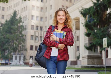 Beautiful Smiling Female Student Holding Notebooks In Hands While Standing In Front Of The Universit