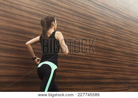 Young Brunette Woman Running In City Near Wooden Wall, Back View, Copy Space