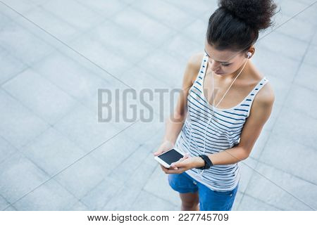 Woman Choose Music To Listen In Her Mobile Phone During Jogging In City, Copy Space, Top View