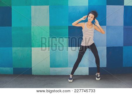 Pensive African-american Woman Posing At Bright Blue Graffiti Wall, While Listening Music, Relaxing