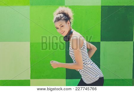 Side View Of Female Athlete Running Against Bright Colorful Graffiti Wall, Listening To Music In Hea