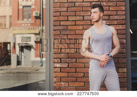 Young Sporty Man Using Smart Watch, Standing At Brick Wall Background, Copy Space. Modern Technology
