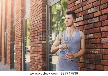 Young Man Runner Is Having Break, Drinking Water While Jogging In City Center, Copy Space