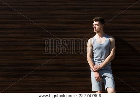 Handsome Sporty Man Leaning On Dark Wooden Wall, Relaxing From Workout Training, Copy Space