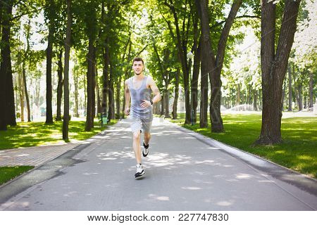Young Sporty Man Running In Green Park During Morning Workout, Copy Space