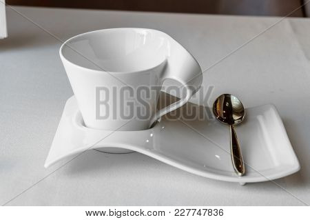 White Cup With Copyspace On A White Saucer With A Teaspoon