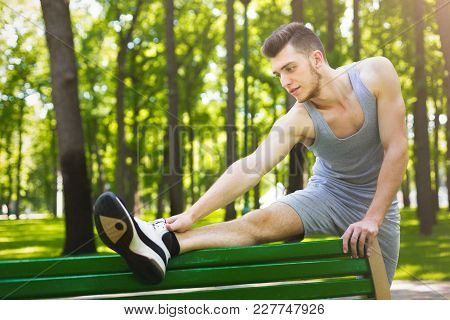 Fitness Man Stretching His Legs Before Running Outdoors. Young Guy Makes Aerobics Exercise On Bench