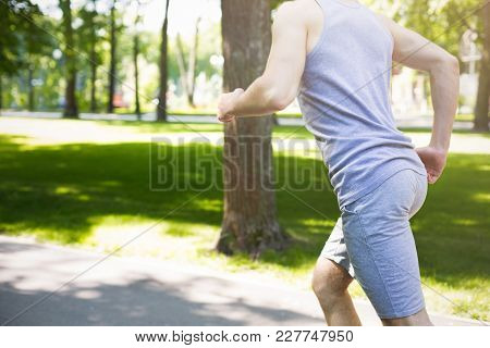 Unrecognizable Man With Sporty Body Running In Green Park During Morning Workout, Copy Space