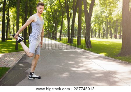 Fitness Man Stretching His Legs Before Running Outdoors. Young Guy Warming Up During Morning Workout
