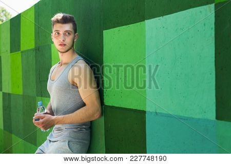 Man Runner Is Having Break, Drinking Water While Jogging In City, Leaning At Green Painted Wall, Cop