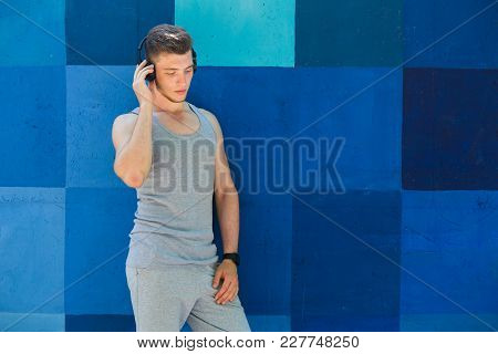 Man In Earphones Listening Favorite Music, Leaning At Bright Blue Graffiti Wall With Closed Eyes, Co