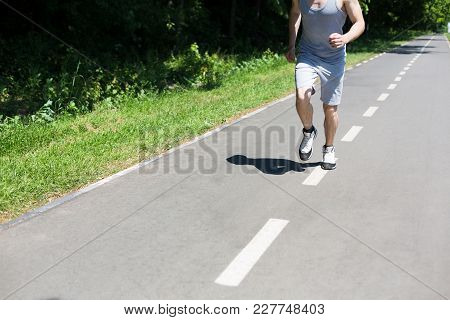 Young Sporty Man Jogging On Treadmill In Park During Morning Workout, Copy Space, Crop