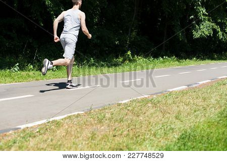 Young Sporty Man Jogging On Treadmill In Park During Morning Workout, Copy Space