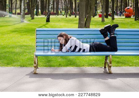 Beautiful Brinette Girl Sitting On A Bench, Dreaming And Writing Her Plans In A Notebook, Relaxing I