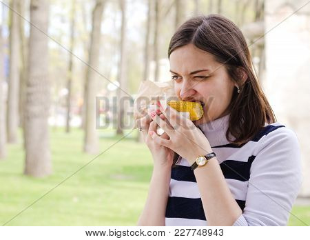 Beautiful Girl Eating Delicious Corn In A Park On A Sunny Spring Day