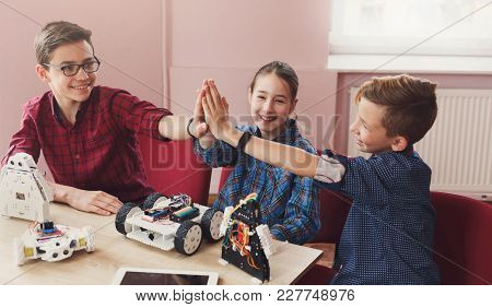 Successful Teamwork. Children Giving Group High-five After Creating Robots At School, Stem Education