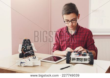 Concentrated Boy Creating Robot At Lab. Early Development, Diy, Innovation, Modern Technology Concep