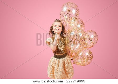 Dreamy Young Girl In Glittering Golden Dress Standing With Balloons And Touching Chin.