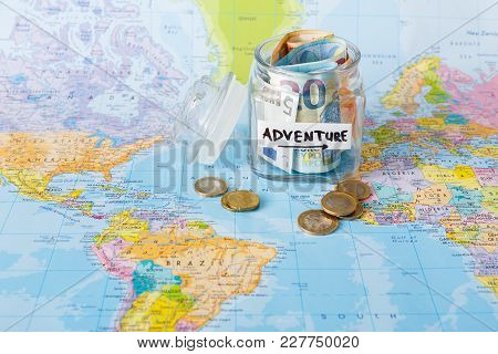 Travel Budget Concept. Money Saved For Vacation In Glass Jar On World Map Background, Copy Space. Ba