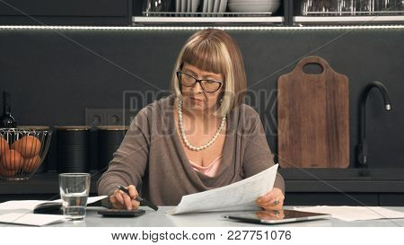 Senior Woman In Glasses Considers Expenses On Calculator