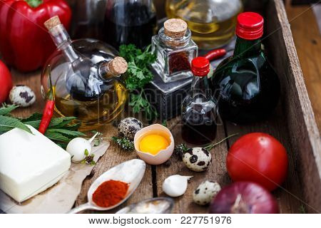 Various Spices, Oils And Sauces Selection On Wooden Background.