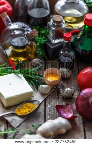 Various Ingredients For Cooking: Oils, Sauces, Spices And Vegetables In A Wooden Box