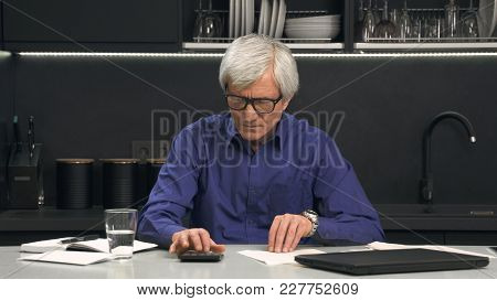 Senior Man In Glasses Considers Expenses On Calculator