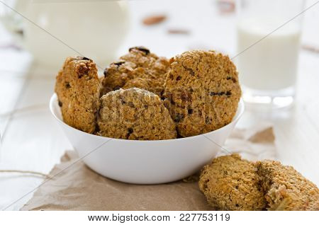 Homemade Oatmeal Cookies With Raisins And Prunes With Jug And Glass Of Milk On White Wooden Backgrou