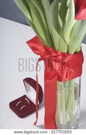 Gifts For Loved Ones. A Bouquet Of Red Tulips Stands In A Glass Vase, Tied With Scarlet Ribbon. Near