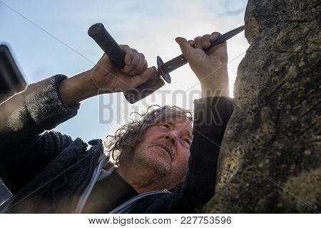 Bottom View Of Sculptor Sculpting With Chisel And Hammer In Stone Under Blue Sky.