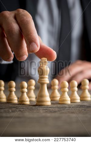 Businessman Wearing Suit Moving The King Piece In A Close Up View With Pawns Visible Behind On The D