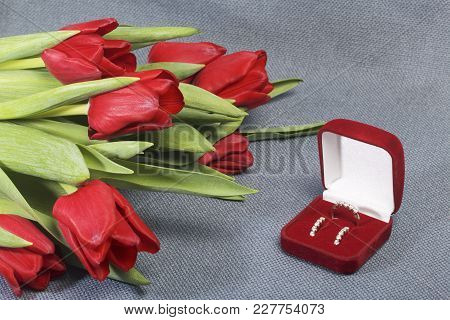 Gifts For Loved Ones. A Bouquet Of Red Tulips. Nearby Is A Red Velvet Box With A Ring And Earrings.