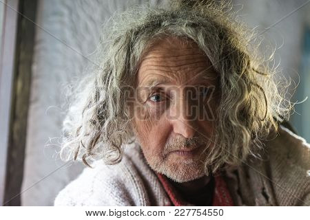 Portrait Of Old Man With Unkempt Long Gray Hair And Stubble Looking Sad.