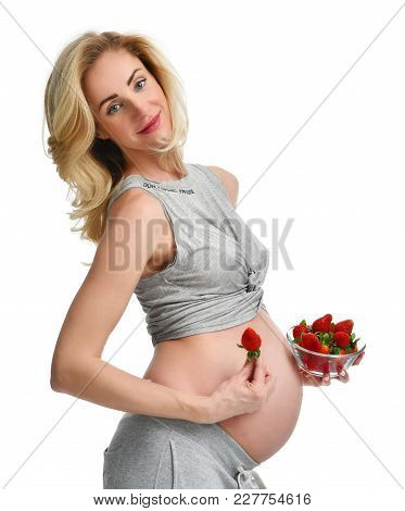 Beautiful Pregnant Woman With Big Belly Eat Strawberries Isolated On A White Background