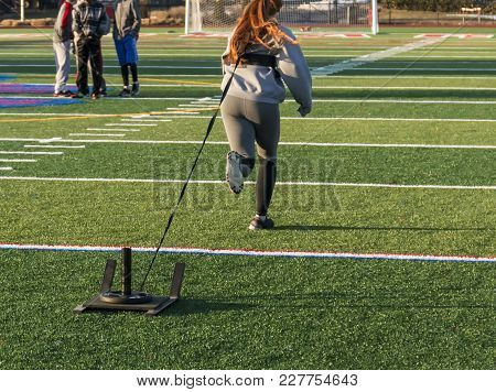 A High School Athlete Is Running Away From The Camera Pulling A Weighted Sled For Strength And Speed