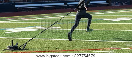 A Runner Is Sprinting, Bounding, Down A Green Turf Field Pulling A Led With 50 Lbs Of Weight On It.