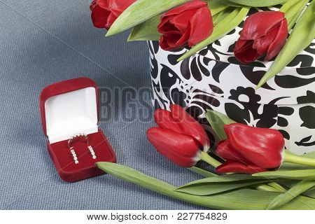 Gifts For Loved Ones. A Bouquet Of Red Tulips Is Scattered On A Corpse With A Pattern Of White And B