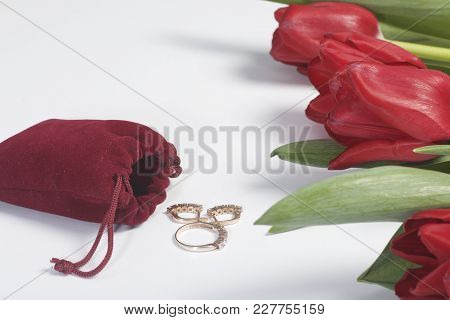 Gifts For Loved Ones. A Bouquet Of Red Tulips Is Scattered On A White Surface. Nearby Is A Red Velve
